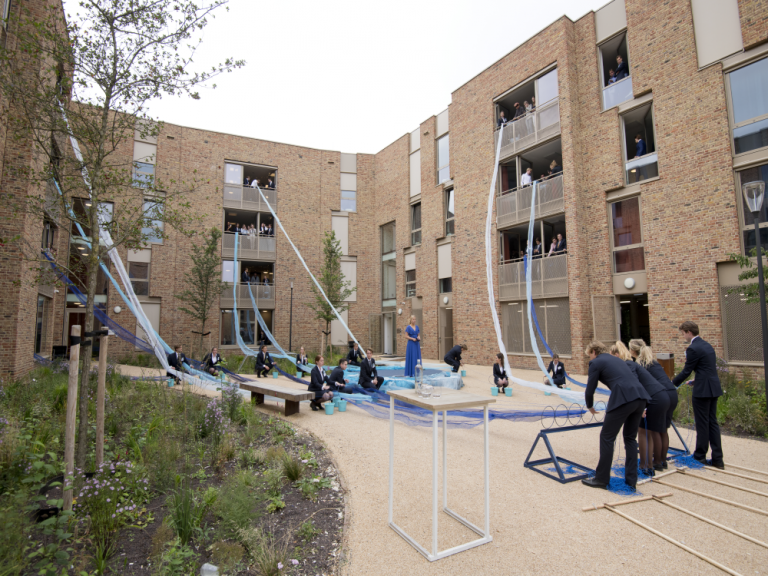 The new student residence is opened by students. Flowing blue organza flows out the windows like a river.