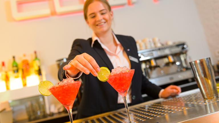 Studente staat achter bar in Le Coin en legt de laatste hand aan een rode cocktail door een schijfje limoen toe te voegen.