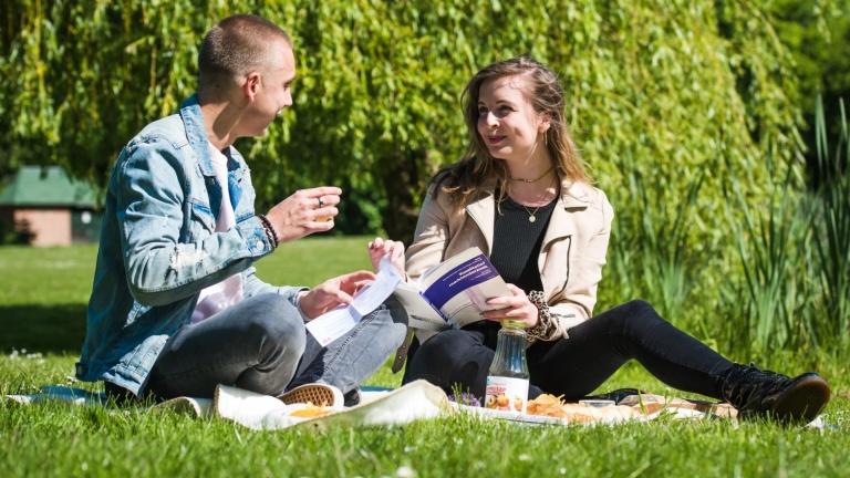 Twee studenten zitten te picknicken én te studeren in het zonnetje in het park van het Teaching Hotel.