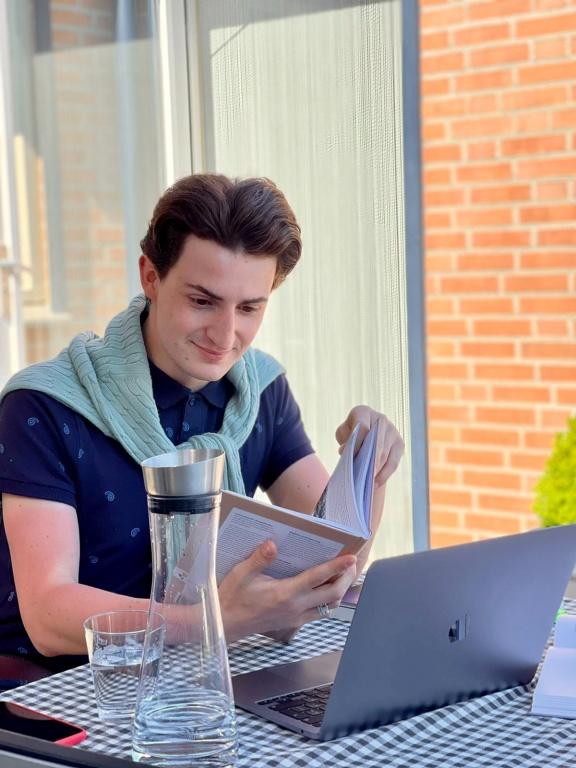 Student zit aan een tafel achter een laptop, heeft een boek in zijn handen en een karaf water op de tafel staan. Draagt een blauwe polo en een groene trui. Het tafelkleed is geblokt.
