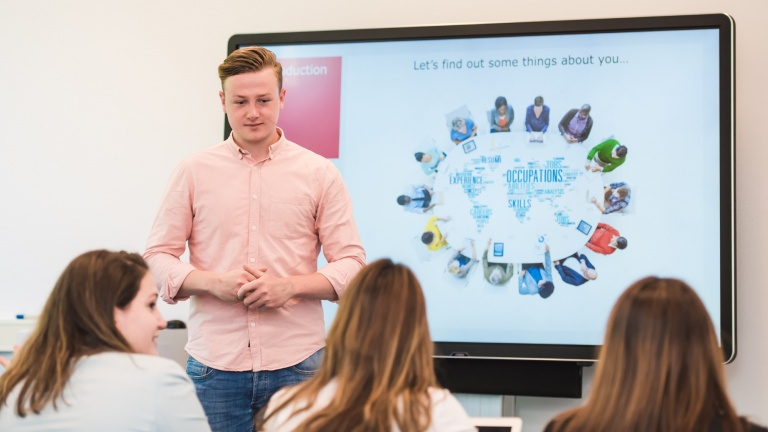 Student stands in front of the smart board in the classroom and gives presentation to his fellow students at the hotel school maastricht.