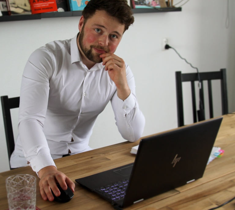 Young man, white shirt, beard, laptop, desk