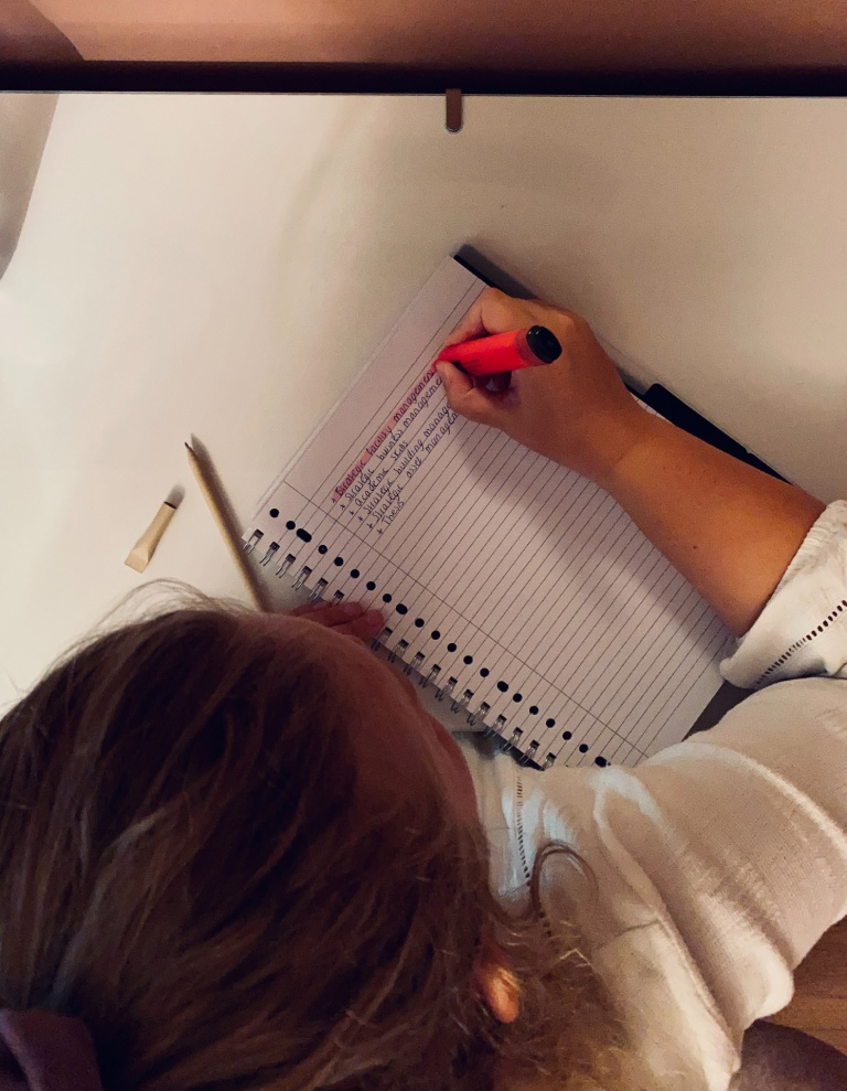 Merel Nijsten writing her to-do list sitting at her desk with a notebook and a pink marker