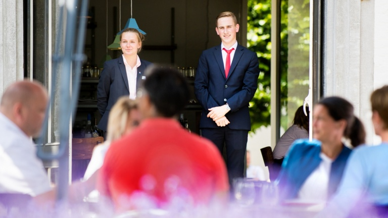 A female and male first-year student keep an eye on the fact that guests on the terrace of the Teaching Hotel lack nothing.