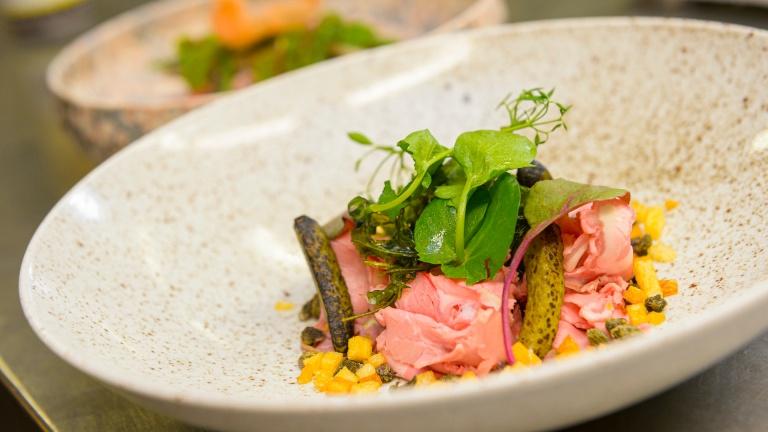 Een kleurrijk zomers voorgerecht met koud vlees klaar om geserveerd te worden in het Teaching Hotel.