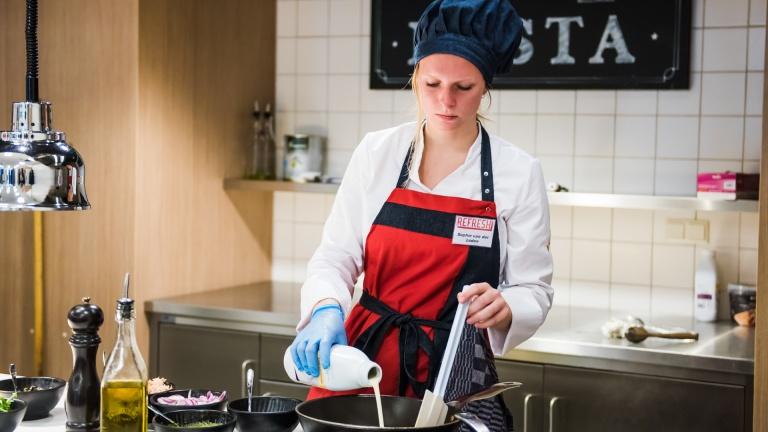 Vrouwelijk studente schenkt melk in een ketel in de keuken van restaurant l'Etoile