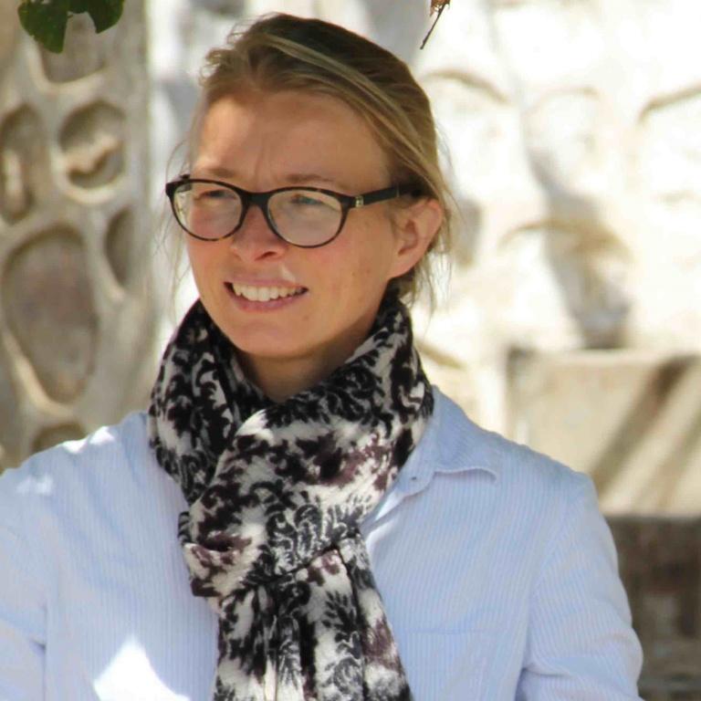 Maaike Kalse blond haar zwarte bril met een wit shirt en een sjaal om
