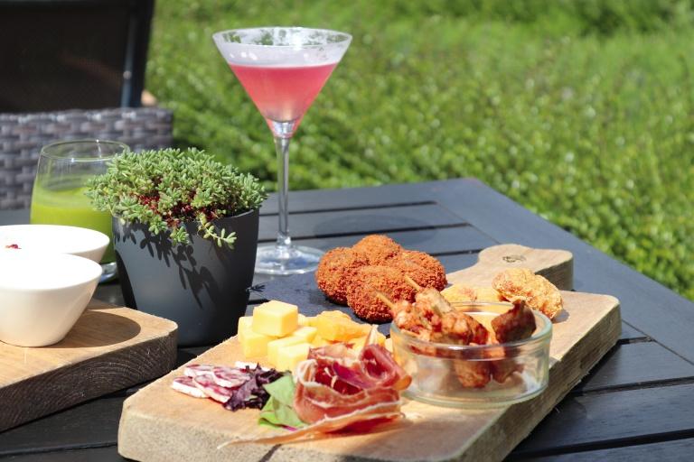 Een borrelplank op een tafel op het terras van het Teaching Hotel met een rode cocktail, bitterballen, kaas en vleeswaren,