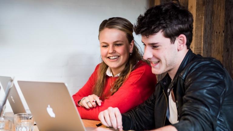 Twee hotelschool studenten zitten lachend achter hun Apple laptop te studeren in een van de rode cabines op de 1e verdieping van het studentenrestaurant Refresh