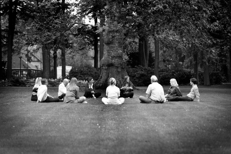 Het team van Hospitality Consultancy zit in een kring op een grasveld en praat met elkaar.